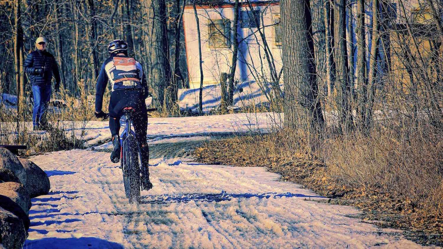 A fast racer leaves a rooster tail of snow in the wake of his fat bike.