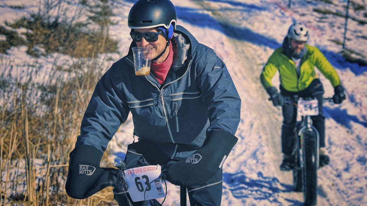 A fat bike rider holds his beer in his teeth after a fast descent during the Fat Cupid Classic.